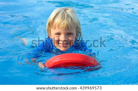 Happy  little boy has fun with floating board  in  swimming pool - stock photo