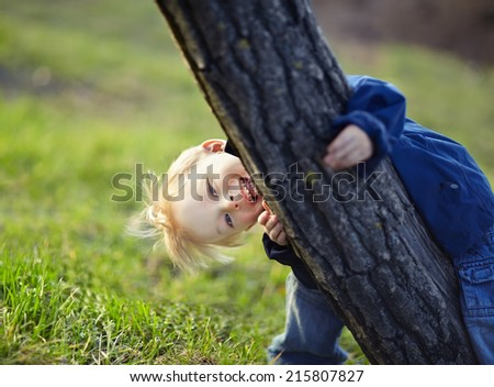 Happy little boy having fun near the tree in the spring park - stock photo