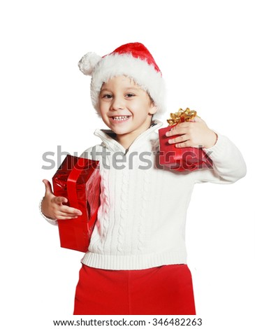 Happy little boy holding Christmas gift boxes in hand wearing santa hat. Isolated on white background. Holidays, christmas, new year, x-mas concept. - stock photo