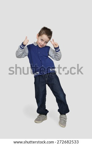 Happy little boy in casual clothes demonstrates that all is good posing on gray background - stock photo
