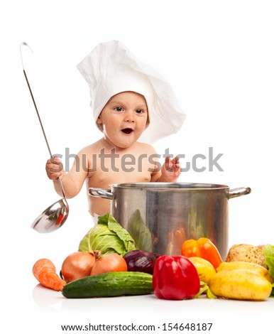 Happy little boy in chef's hat with ladle, casserole, and vegetables  - stock photo