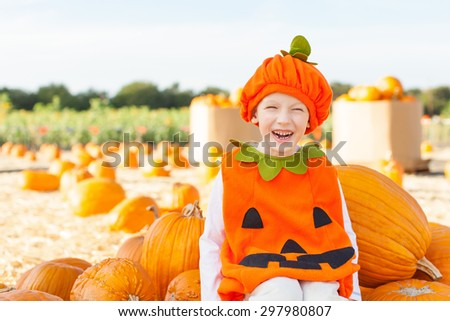 happy little boy in pumpkin costume enjoying autumn time and pumpkin patch - stock photo