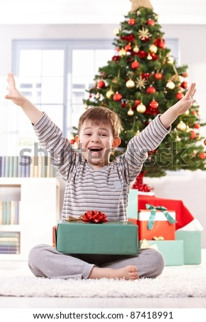 Happy little boy in pyjama getting present at christmas, laughing at camera with arms wide open.? - stock photo