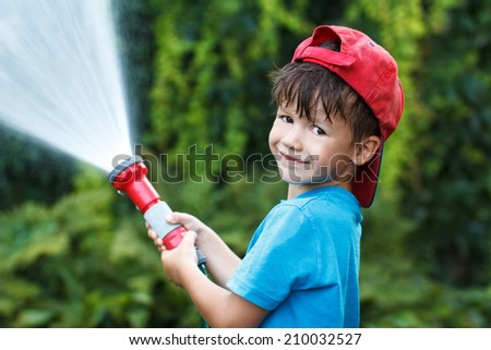 Happy little boy in red cap pours water outdoor - stock photo