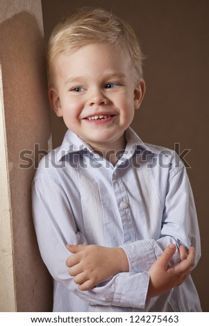 Happy little boy in shirt posing at the wall - stock photo