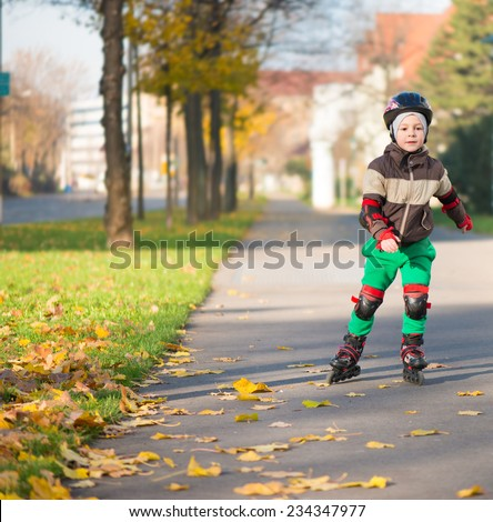 Happy little boy in sunny day on roller skates - stock photo
