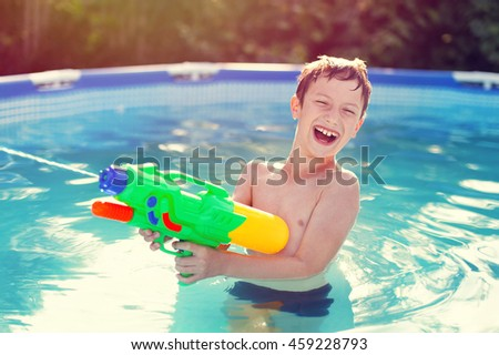 Happy little boy laugh and shoot with squirt gun in sunset - stock photo