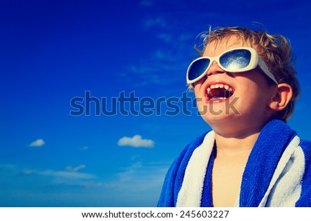 happy little boy laugh wrapped in beach towel on sky - stock photo