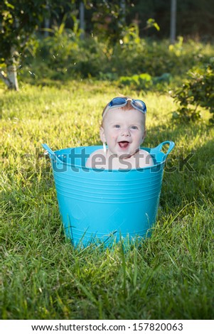 Happy little boy looking out from swimming pool - stock photo