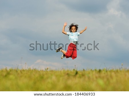 Happy little boy on summer grass meadow in nature jumping - stock photo