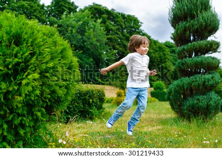 happy little boy playing and jumping in the park outdoors - stock photo