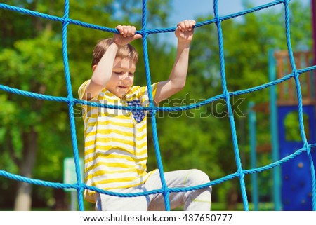 Happy little boy playing at playground in summer day - stock photo