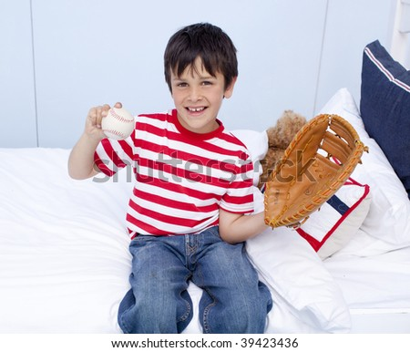 Happy little boy playing baseball in his bedroom - stock photo