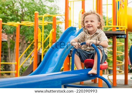 Happy little boy playing on the playground at the day time - stock photo