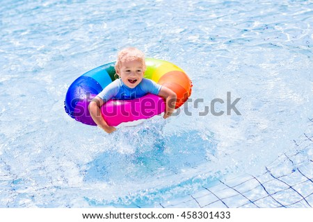 Happy little boy playing with colorful inflatable ring in outdoor swimming pool on hot summer day. Kids learn to swim. Children wearing sun protection rash guard relaxing in tropical resort - stock photo