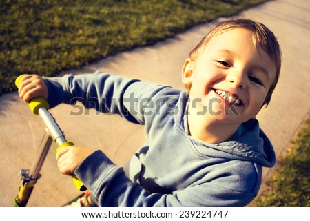 happy little boy playing with his scooter at playground - stock photo