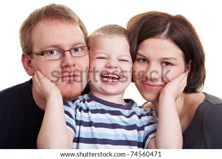 Happy little boy pressing his parents cheeks against his own - stock photo