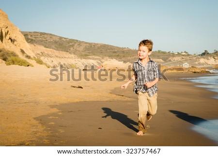 Happy little boy running around at the beach, enjoying himself - stock photo