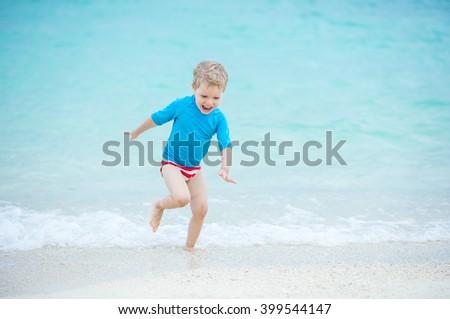 Happy little boy running in breaking waves on the beach - stock photo