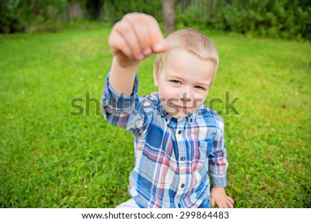 Happy little boy showing something on his fingers and green outdoor background - stock photo