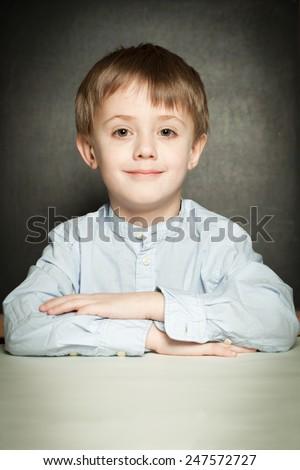 Happy little boy sitting in school classroom - stock photo