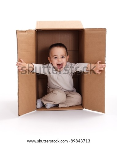 Happy little boy sitting inside cardboard box, opening - stock photo