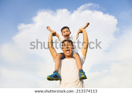 happy little boy  sitting on father's shoulder - stock photo