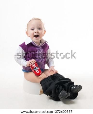 Happy little boy sitting on the pot - stock photo