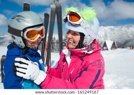 Happy little boy to ski in ski goggles and a helmet with his mother - stock photo