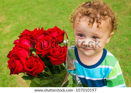 happy little boy with a bouquet of red roses - stock photo