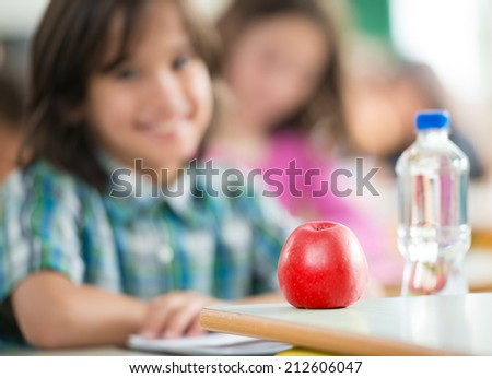 Happy little boy with apple and water bottle sitting in classrom and smiling - stock photo