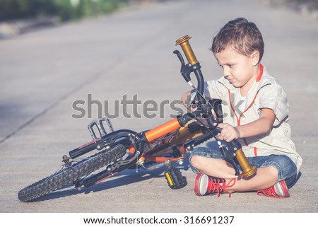 Happy little boy with bicycle sitting on road  at the day time - stock photo