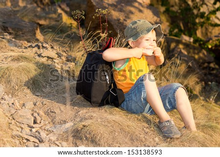 Happy little boy with his backpack sitting on the ground on a mountain slope taking a break from hiking - stock photo