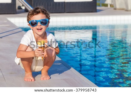 happy little boy with ice cream sitting near a swimming pool at the day time. - stock photo
