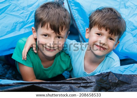 Happy little brothers in tent, outdoor portrait - stock photo