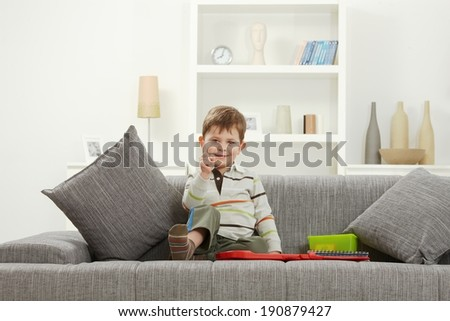 Happy little caucasian kid with toys sitting on sofa, looking at camera, smiling. Home indoors. - stock photo