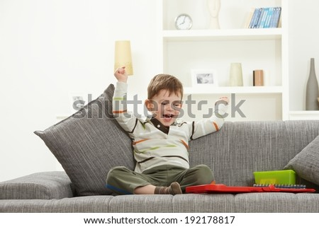 Happy little caucasian kid with toys sitting on sofa, looking at camera, smiling. Home indoors, hands in air. - stock photo