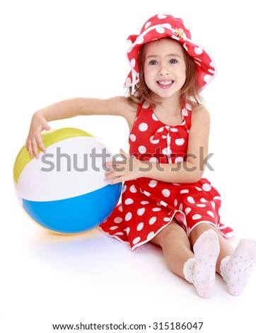 Happy little charming girl in summer dress with polka dots sitting on the floor and hugging a large beach striped ball . The girl is resting with his family at a seaside resort-Isolated on white - stock photo