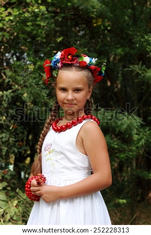 Happy little child, adorable blonde girl dressed in national Ukrainian costume wearing wreath of flowers, peacefully playing in beautiful field in Ukraine - make love not war concept - stock photo