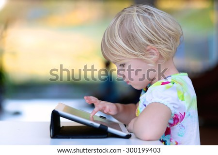 Happy little child, adorable blonde toddler girl enjoying modern generation technologies playing indoors using tablet pc with touchscreen - stock photo