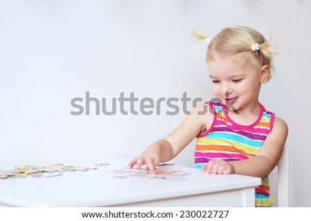 Happy little child, adorable blonde toddler girl, having fun playing with jigsaw puzzle assembling pieces of picture together sitting indoors at small white table - stock photo