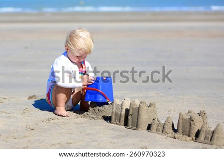 Happy little child, adorable blonde toddler girl wearing colorful dress playing with plastic toys on the beach at North Sea building sand castles - stock photo