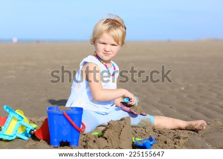 Happy little child, adorable blonde toddler girl wearing colorful necklace playing on the beach at North Sea building sand castles using plastic toys - stock photo