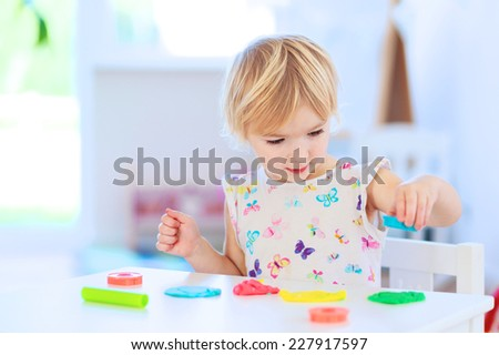 Happy little child, adorable creative toddler girl playing with dough, colorful modeling compound, sitting at white table in bright sunny room with big window at home or kindergarten - stock photo