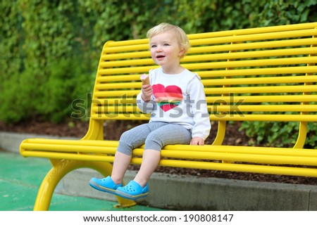 Happy little child, adorable toddler girl with blond curly hair in casual outfit enjoying ice cream outdoors sitting on yellow bench in amusement park on a sunny summer day - stock photo