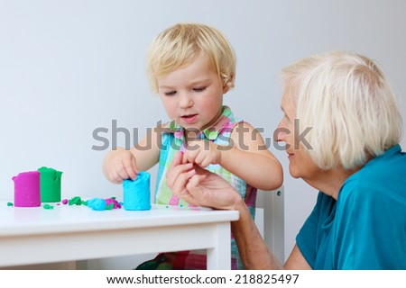 Happy little child, adorable toddler preschooler girl creating using dough, colorful modeling compound sitting at small table together with grandmother at home or senior caregiver at kindergarten - stock photo