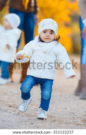 happy little child, baby girl laughing and playing in the autumn on the nature walk outdoors. happy little girl have fun playing with fallen golden leaves - stock photo