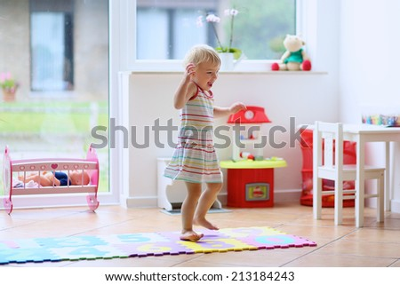Happy little child, cute blonde toddler girl having fun dancing indoors in a sunny white room at home or kindergarten - stock photo