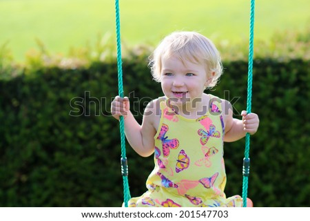 Happy little child, cute blonde toddler girl having fun on the swing in the garden at the backyard of the house on a sunny summer day - stock photo
