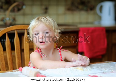 Happy little child, cute blonde toddler girl, sitting at the table in classic traditional wooden kitchen making delicious cookies - stock photo